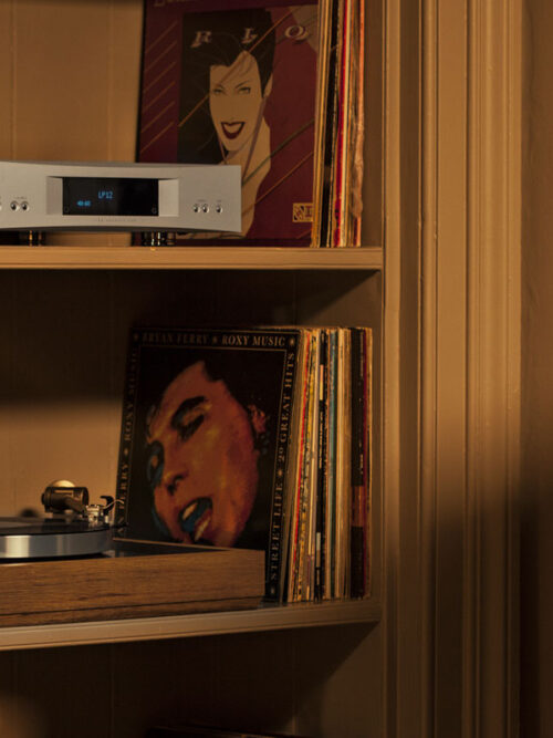 Stunning turntable sits on the shelf in a home playing music softly.